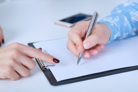 The employer forces the employee to write a letter of resignation. Just hands over the table. Фото со стока
