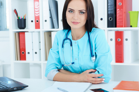 Young female medical doctor is waiting for patient to examine. Physician reception concept.