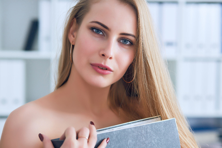 Beautiful young secretary hides her nakedness for a folder on an office background. Harassment concept.