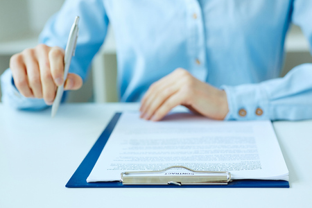 Hands of business woman signing the contract document with pen on desk close-up. Selective focus image on sign a contract. Standard-Bild