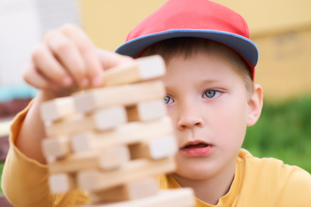 Caucasian kid is playing wood blocks tower game for practicing physical and mental skill. Emotional photos. Stockfoto