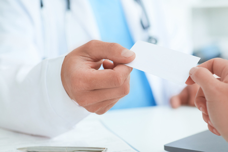 Male doctors hand give white blank calling card to woman closeup in office. Physical, disease prevention, examine patient, instrument shop, healthy lifestyle, family doctor concept Archivio Fotografico