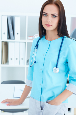 Beautiful female medicine doctor standing rests her hand on the table in office. Medical help or insurance concept. Standard-Bild