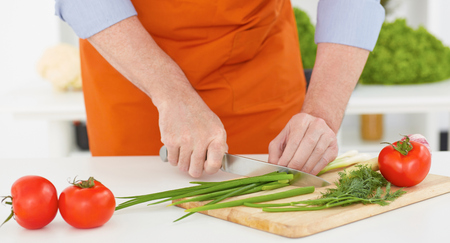 Close up image of male hands chopping green onions in the kitchen at home.