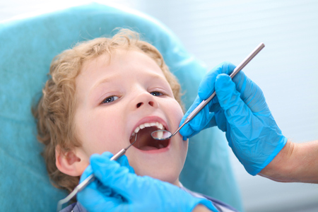 Close-up of little boy opening his mouth wide during inspection of oral cavity by dentist. Medical cure and tests advertisement concept.