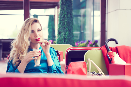 Blonde woman in the blue dress sitting at the cafe and drinking milk cocktail. Beauty portrait. 写真素材