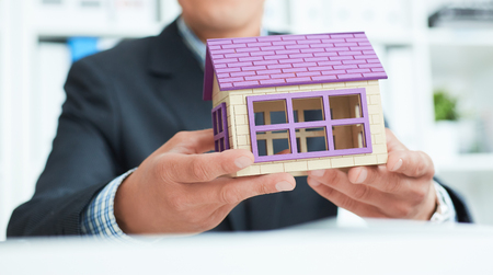 Middle section of businessman holding home model. Loan concept