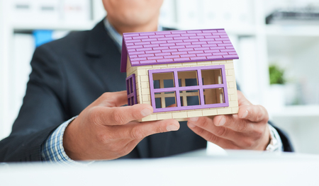 Businessman in suit holding house model. Loan or rent concept. Stock Photo
