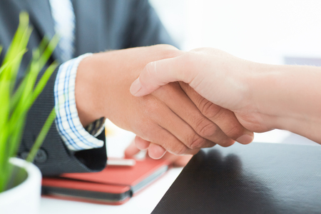 Businessman and woman shake hands as hello in office closeup. Friend welcome, introduction, greet or thanks gesture, strike a bargain on deal concept