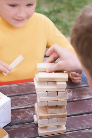 Little caucasian boys playing wood blocks tower game for practicing physical and mental skill. Emotional photos.