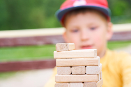 Little caucasian boy is playing wood blocks tower game for practicing physical and mental skill. Emotional photos. Stockfoto