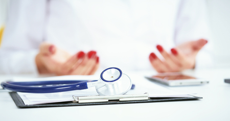 Stethoscope, medical prescription form are lying against the doctor and patient discussing health exam results