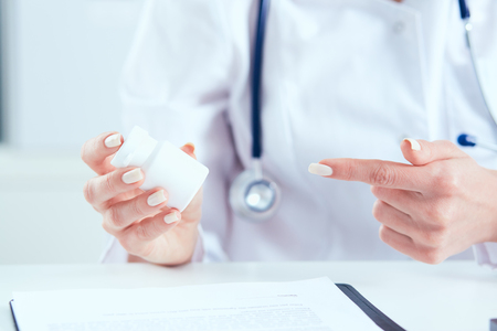 Young female medicine doctor sitting in front of working table holding jar of pills and explains to the patient how to take medication. Medical and pharmacy concept