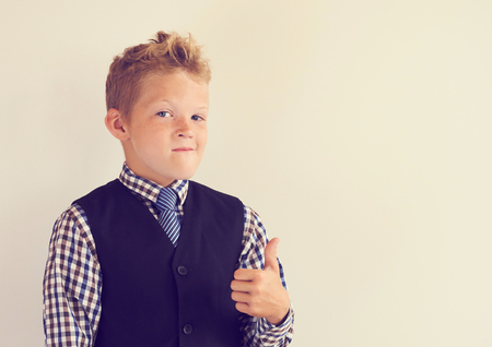 Smiling little schoolboy showing thumb up standing near the white blackboard. Stock Photo