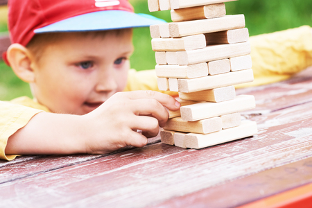 Caucasian kid is playing wood blocks tower game for practicing physical and mental skill. Reklamní fotografie