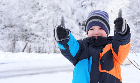 Cute Caucasian boy giving thumbs up, playing and laughing on snowy winter walk in nature. Frost winter season.