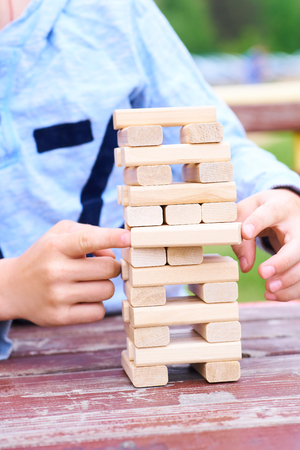 Middle section of the kid playing wood blocks tower game for practicing physical and mental skill.