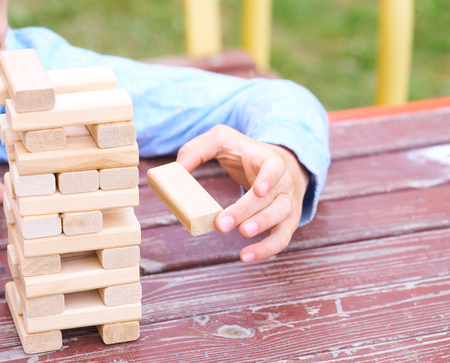 Little caucasian boy is playing wood blocks tower game for practicing physical and mental skill. Boy's hand pulls a wooden block from the tower. Educational games for children and the whole family. Stockfoto