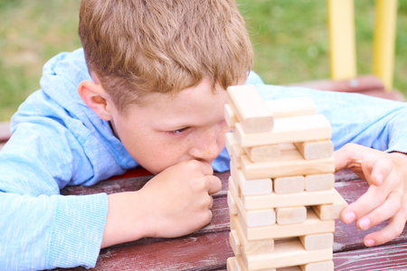 Caucasian kid is playing wood blocks tower game for practicing physical and mental skill. Stockfoto