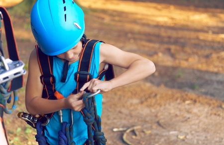 Little boy in climbing equipment and a safety helmet is taught safety in a rope park. Hobby, active lifestyle concept