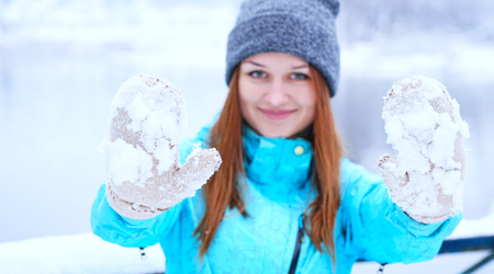Smiling Caucasian girl in gray knitted mittens and a hat. Snowy forest in the background. Winter. Snow around. Stock Photo
