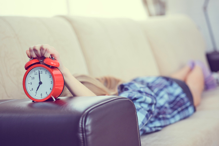 Young girl lies on the couch and stretches her hand to the red alarm clock to turn it off. Late wake up. Imagens