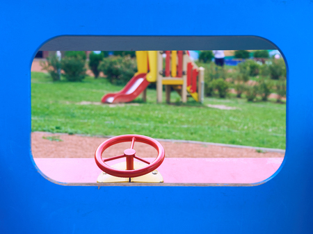 Wooden toy car in the playground for children. Red metal steering wheel of childrens wooden car on the playground closeup.