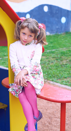 Little Caucasian child girl looking seriously being on the playground. Archivio Fotografico