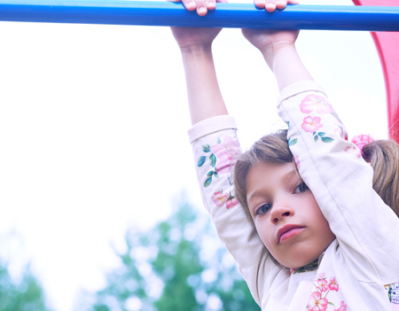 Portrait of cute Caucasian litte girl wearing white dress with flowers hanging on monkey bars on a summer day. Girl looking at camera smiling. Green leaves a seen in the background. Stock Photo