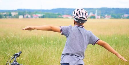 Back view of teenager boy in protective helmet spread his arms out like a bird standing next to his bike in park on summer day. Childrens outdoor activities in summer.