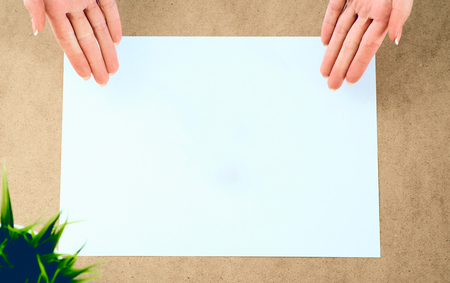 Blank paper lying on the table and waiting for idea with womans hands over it .