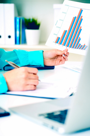 Business woman working with financial data holding sheet of paper with financial figures in hand and make notes in clipboard. Business financial and accounting concept. Banque d'images