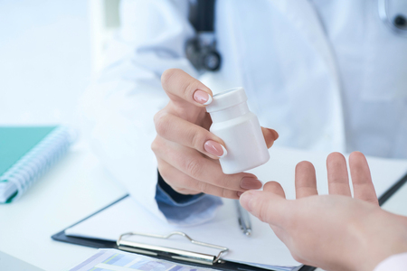 Female doctor hands gives jar of pills to patient hand closeup.