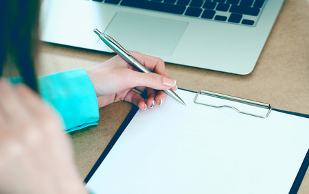 Stressed business woman write in clipboard in the surrounding