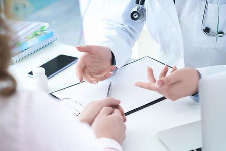 Patiënt luistert aandachtig naar een vrouwelijke arts die de symptomen van de patiënt uitlegt of een vraag stelt terwijl ze samen bespreken in een consult.