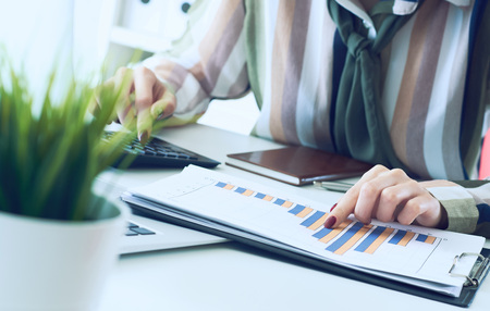 A womans hand pointing on summary report chart and calculate finance in office close-up.