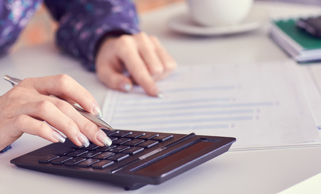Close up of female accountant or banker hand making calculations. Savings, finances and economy concept