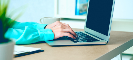 Side view and close up of womans hands typing on laptop keyboard in office interior. 스톡 콘텐츠