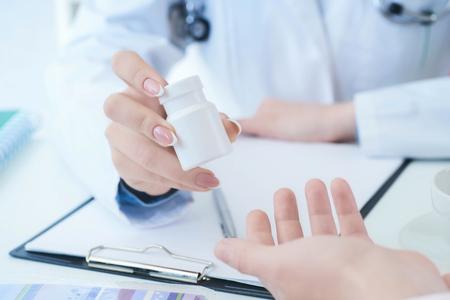 Ärztinhände geben der geduldigen Handnahaufnahme ein Glas Pillen.