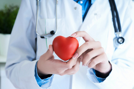 Female medicine doctor hold in hands red toy heart close -up. Cardio therapeutist student education concept