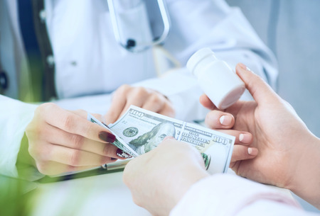 Female doctor hands gives jar of pills to patient hand and receives money in return closeup.