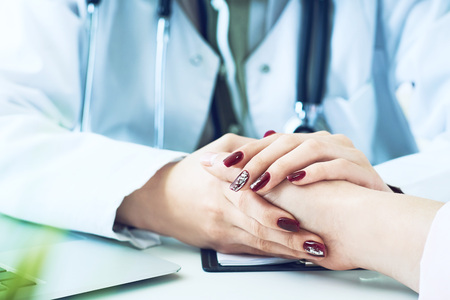 Cropped image of female therapist holding patients hands during the consultation. Medical ethics and trust concept 写真素材