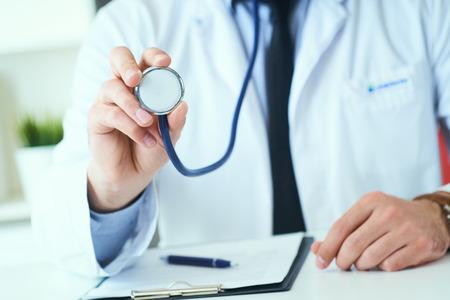 Cerca de la mano de un médico, sosteniendo un estetoscopio extendido hacia el espectador. Medic shop o store, prevención física y de enfermedades, consultor er, 911, medición del pulso, concepto de estilo de vida saludable