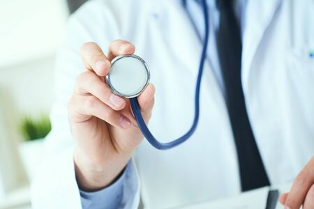Close up of a doctors hand, holding a stethoscope outstretched towards the viewer. Medic shop or store, physical and disease prevention, er consultant, 911, pulse measure, healthy lifestyle concept Imagens