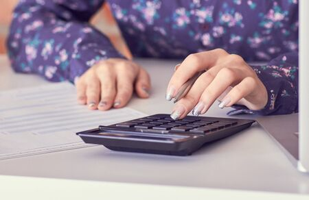 Close up of female accountant or banker hand making calculations. Savings, finances and economy concept Zdjęcie Seryjne