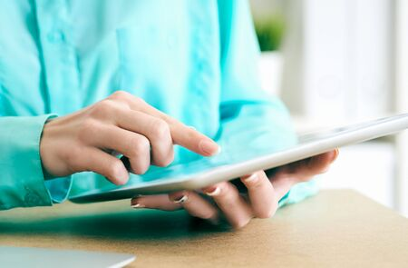 Close-up of female hands working with tablet computer. Woman using social network, texting and blogging.