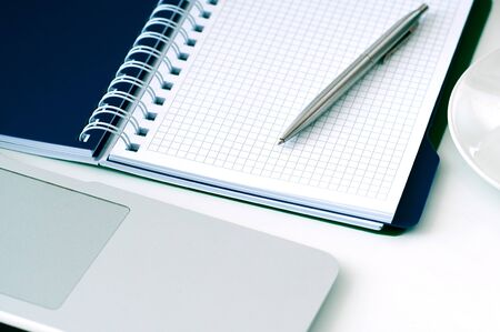 Closeup of white desktop with laptop, coffee cup, notepads, pen, calculator and other items. Zdjęcie Seryjne