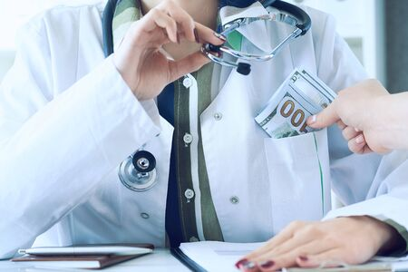 Medicine doctor receiving large amount of dollar banknotes as a bribe. Corruption in Health Care Industry concept. Imagens
