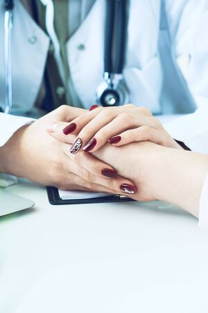Cropped image of female therapist holding patients hands during the consultation. Medical ethics and trust concept Zdjęcie Seryjne