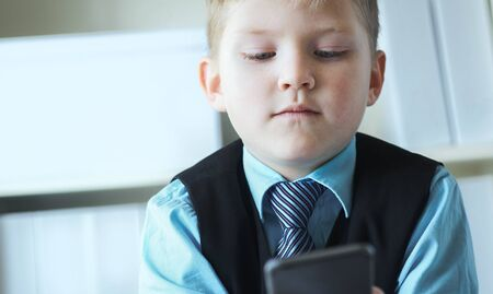 Serious little boy looking at the phone at fathers table in office. Boy in business suit playing boss. Stockfoto